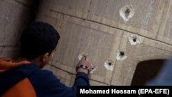 Мар Мина шіркеуінің сыртқы қабырғасында қалған оқ іздерін санап тұрған адам. Египет, 29 желтоқсан 2017 жыл.