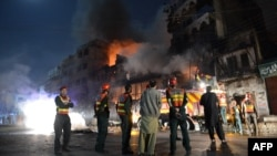 Pakistani rescue and security personnel gather in front of a burning market after sectarian clashes near a Sunni mosque during the Shi'ite Muslim procession in Rawalpindi on November 15.