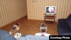 Пострадавшие от бытового насилия женщины смотрят телевизор в кризисном центре. Караганда, 7 июня 2013 года.