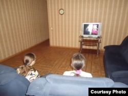 Уақытша паналау орнында телевизор көріп отырған әйелде. Қазақстан, 7 маусым 2013 жыл. (Көрнекі сурет)