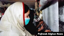 Women weaving carpets in Afghanistan
