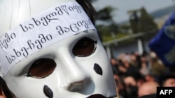 A masked activist at an anti-Saakashvili rally in front of the parliament building in Tbilisi