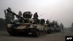 FILE: Pakistani army tanks form a column during a ground military operation against Taliban militants in North Waziristan.