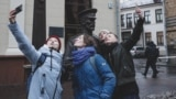 Four actresses from Minsk's Free Theater stage a flash mob near a controversial police statue in the Belarusian capital