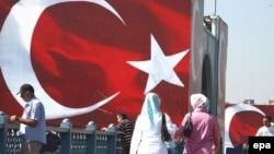 Стамбулдағы Түркия туы ілінген жерден өтіп бара жатқан адамдар. (Көрнекі сурет)