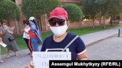 Участница акции у Дома министерств с листовкой с призывом ввести смертную казнь за педофилию. Нур-Султан, 3 августа 2020 года.