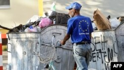 Macedonia -- A man wearing a tee-shirt with the European Union logo collects plastic bottles from trash-containers in the centre of Skopje, 24Jun2013