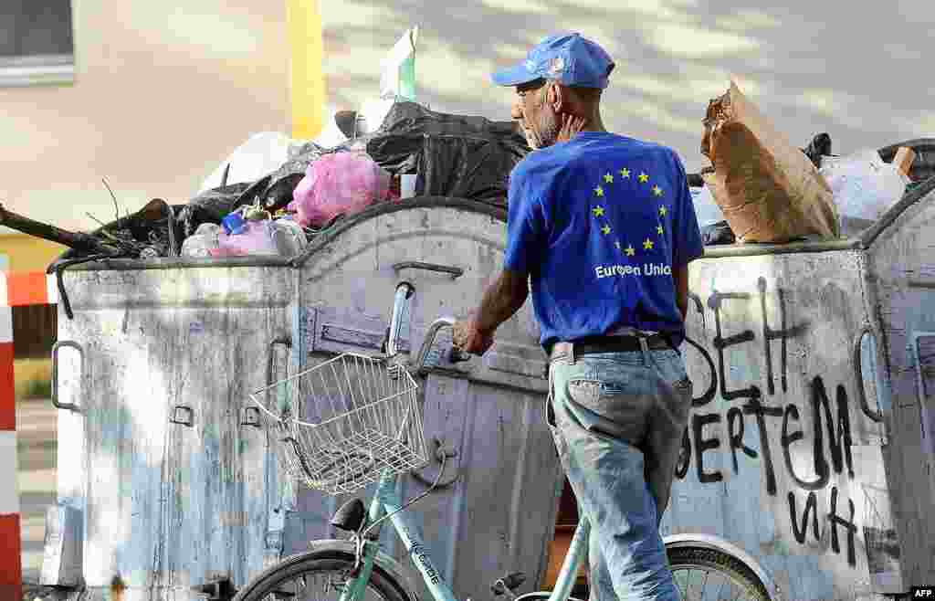 A man wearing a T-shirt with the European Union logo collects plastic bottles from trash containers in the center of Skopje, Macedonia. (AFP/Robert Atanasovski)