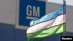 Uzbekistan -- An Uzbek flag flies in front of the General Motors logo at the General Motors Powertrain-Uzbekistan plant in Tashkent, 31Aug2012