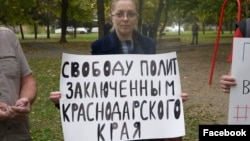 "Yana Antonova holds a sign reading: ""Freedom to political prisoners of Krasnodar region""."