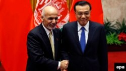 Chinese Prime Minister Li Keqiang and Afghan President Ashraf Ghani (L) pose for pictures during their meeting at the Great Hall of the People in Beijing, October 29, 2015.