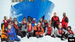 "A picture made available on December 29 shows passengers in front of the ""Akademik Shokalsky,"" which got stuck in Antarctic ice, prompting international rescue efforts."
