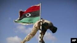 Солдат заменяет флаг Каддафи знаменем повстанцев на одном из КПП