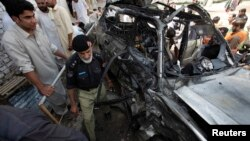 A policeman and residents gather near a damaged car at the site of the bomb blast near a religious school in Peshawar on May 24.