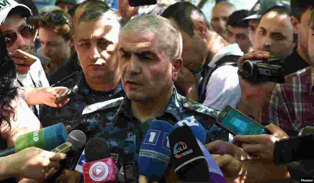 Заместитель начальника полиции Армении Унан Погосян беседует с журналистами возле захваченного здания полиции в Ереване.