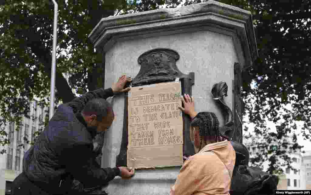 A banner is taped over the inscription on the pedestal of the toppled statue of Edward Colston in Bristol, England, Monday, June 8, 2020. The toppling of the statue was greeted with joyous scenes, recognition of the fact that he was a notorious slave trader — a badge of shame in what is one of Britain's most liberal cities.