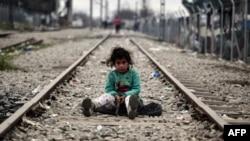 Девочка из семьи беженцев играет посреди железнодорожных рельсов на греческо-македонской границе. 7 марта 2016 года.