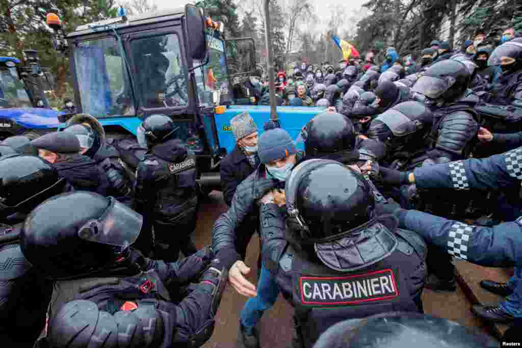 Moldovan law enforcement officers block a tractor during a rally of farmers at a rally demanding government support and financial aid in Chisinau. (Reuters/Stringer)