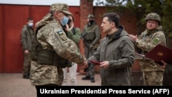 Ukrainian President Volodymyr Zelenskiy (right) shakes hands with a serviceman in the town of Zolote in the Luhansk region on April 8.