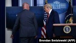 Президент Трамп покидает комнату для брифингов.