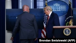Президент США Дональд Трамп (справа) покидает комнату для брифингов.