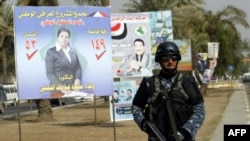 An Iraqi security officer patrols a street past provincial election posters.