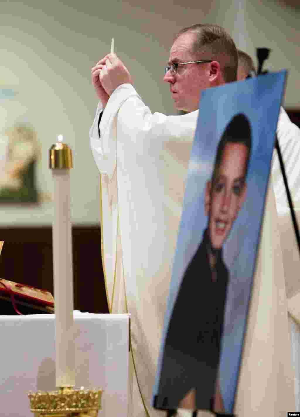 Father Sean Connor conducts a mass to celebrate the young life of Martin Richard of Dorchester in Boston, Massachusetts, on June 9, 2013.