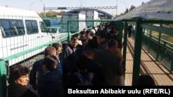 Қырғызстанның Қазақстанмен шекарасындағы өткізу бекетінде кезекте тұрған адамдар. 12 қазан 2017 жыл.