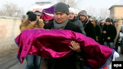 A Kyrgyz man carries the body of a child killed in the crash of a Turkish cargo plane during a funeral ceremony outside Bishkek on January 17.