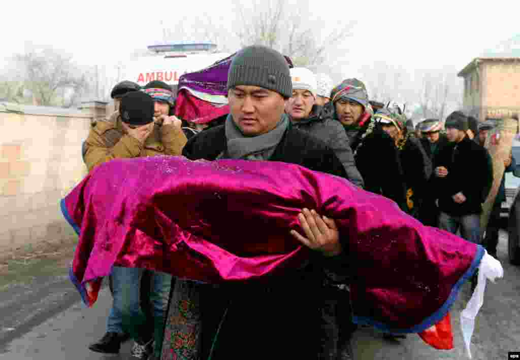 A man carries a dead child's body during a burial ceremony outside Bishkek, Kyrgyzstan. A Turkish Boeing 747-400 cargo plane crashed into a village near the Kyrgyz capital, destroying 32 houses and killing at least 38 people. (epa/Igor Kovalenko)