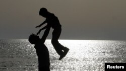 Albania - A father plays with his son on a beach facing the Adriatic sea, near the city of Durres, some 40 km (25 miles) from Tirana, 28Apr2013