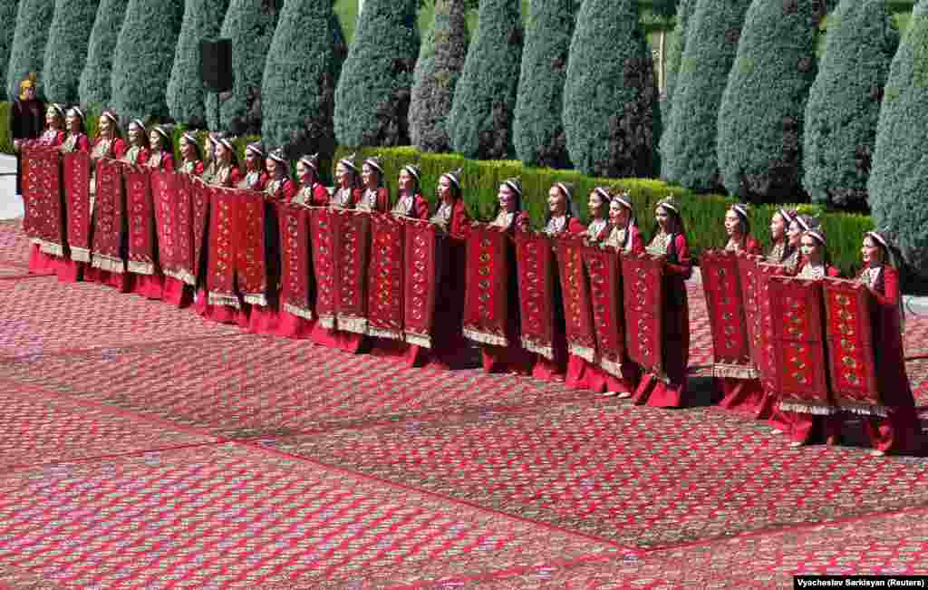 Женщины в традиционной одежде принимают участие в праздновании национального Дня туркменского ковра в Ашхабаде, Туркменистан, 30 мая 2021 года.