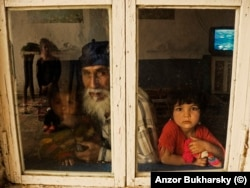 A family peers out of a window in the Romany village near Bukhara.