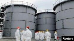 Жапонияның Фукусима АЭС-інде залалсыздандыру жұмыстарын атқарып жатқан мамандар. (Көрнекі сурет)