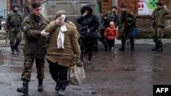 Український військовий медик веде поранену внаслідок артобстрілу жінку, Артемівськ, 29 січня 2015 року