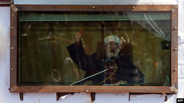 Islamic cleric Muhammad Tahir-ul-Qadri addresses his audience behind bulletproof glass at a rally in Islamabad on January 16.