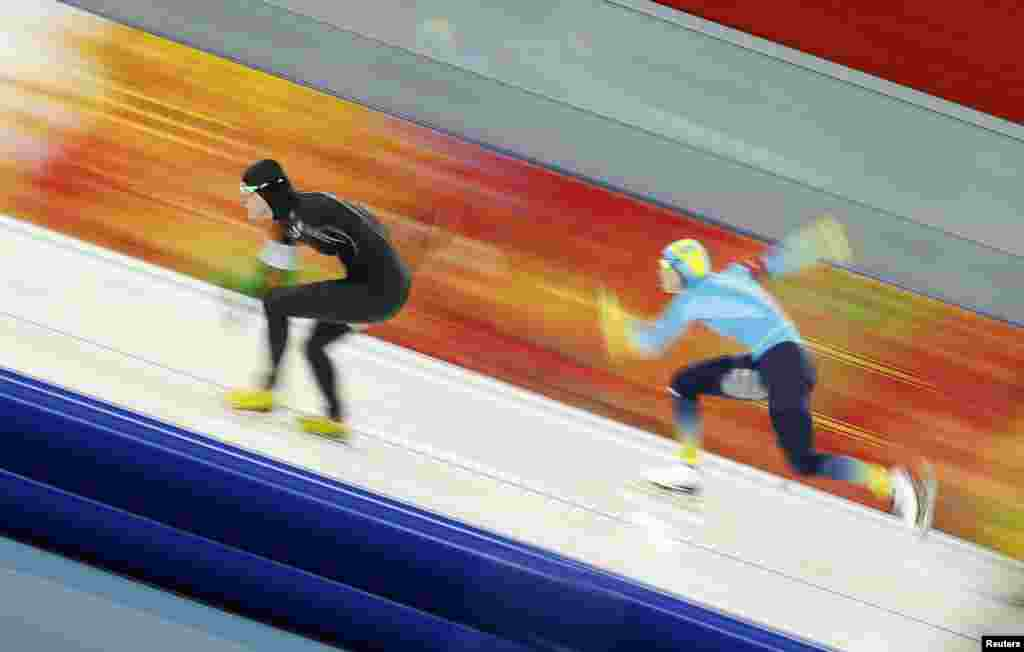 Lauren Cholewinski of the United States leads Kazakhstan's Yekaterina Aydova during the women's 500 metres speed skating race at the Adler Arena.