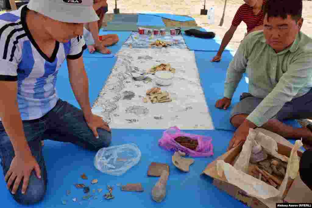 За время изучения городища археологи находили изделия из керамики, металла, кости. Часть находок нынешнего сезона они достали из картонной коробки и разложили перед корреспондентом Азаттыка для фотографирования.