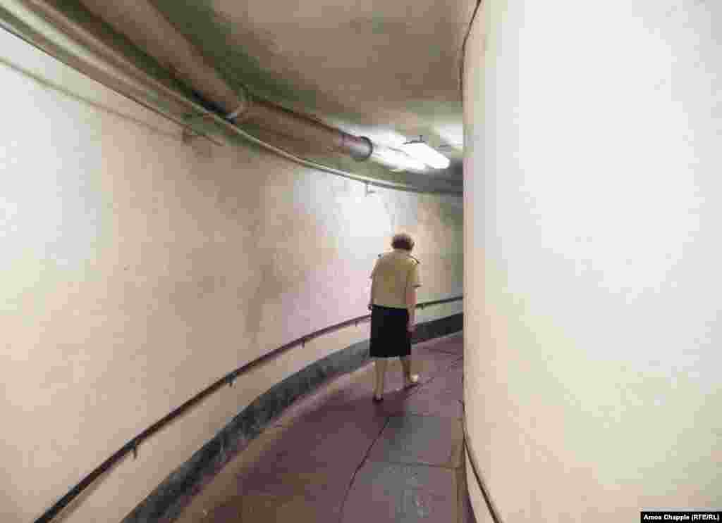"A woman walks in a corridor of the bunker. Kinder told RFE/RL: ""during the [1991 coup attempt] I was in a different city with two young kids and a plane flew over dropping leaflets saying 'we have a new government, you shouldn't rebel.'"""