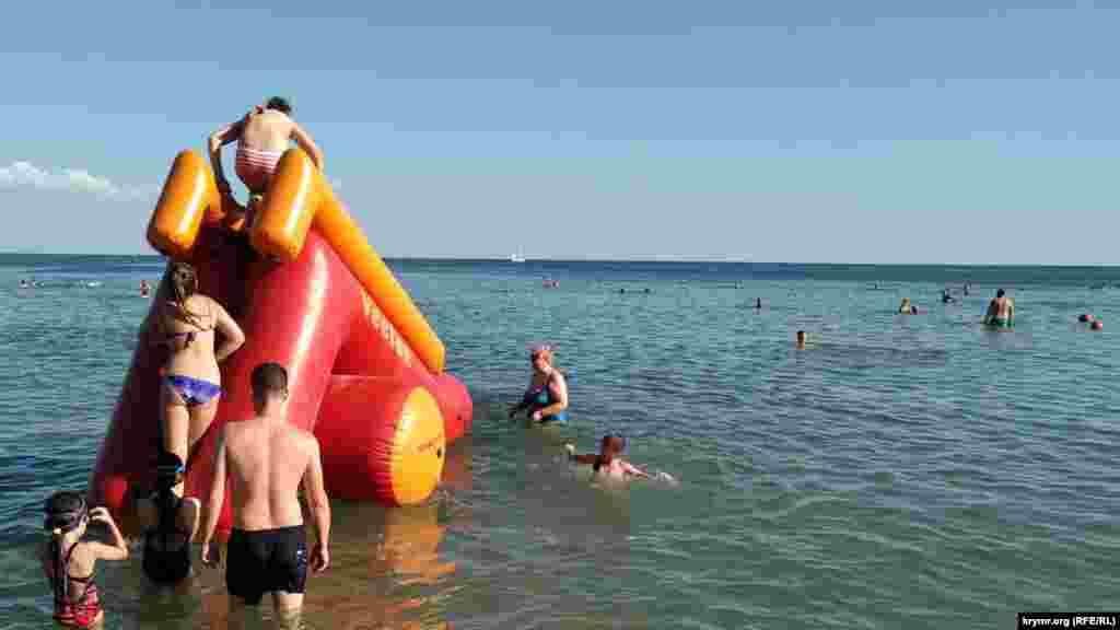 Така ж ситуація спостерігається і біля однієї з пляжних розваг. У чергу на безкоштовну надувну гірку відпочивальники дистанції не дотримуються. Кореспондент Крим.Реалії також не помітив, щоб поверхні гірки, за які люди беруться руками, хто-небудь дезинфікував. Про інші пляжі Євпаторії – читайте тут