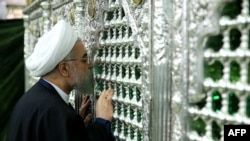 Iranian President Hassan Rohani kisses a religious shrine while visiting the holy city of Qom on February 25.