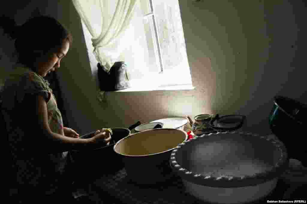 Мольдир моет посуду. Работая по хозяйству, девочка поет. Репортеры Азаттыка слышали, как она пела песню о матери.