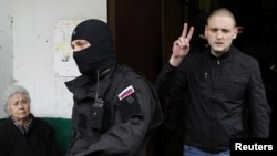 Russian opposition leader Sergei Udaltsov (right) gestures as he is escorted from his apartment after being detained in Moscow on October 17.