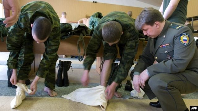 "Young conscripts of the Kremlin regiment are taught how to use the traditional ""portyanki,"" or footwraps, in the Moscow barracks. (2007 photo)"