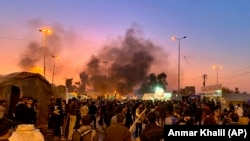 Smoke rises from the sites of anti-government protests in Najaf, February 5, 2020