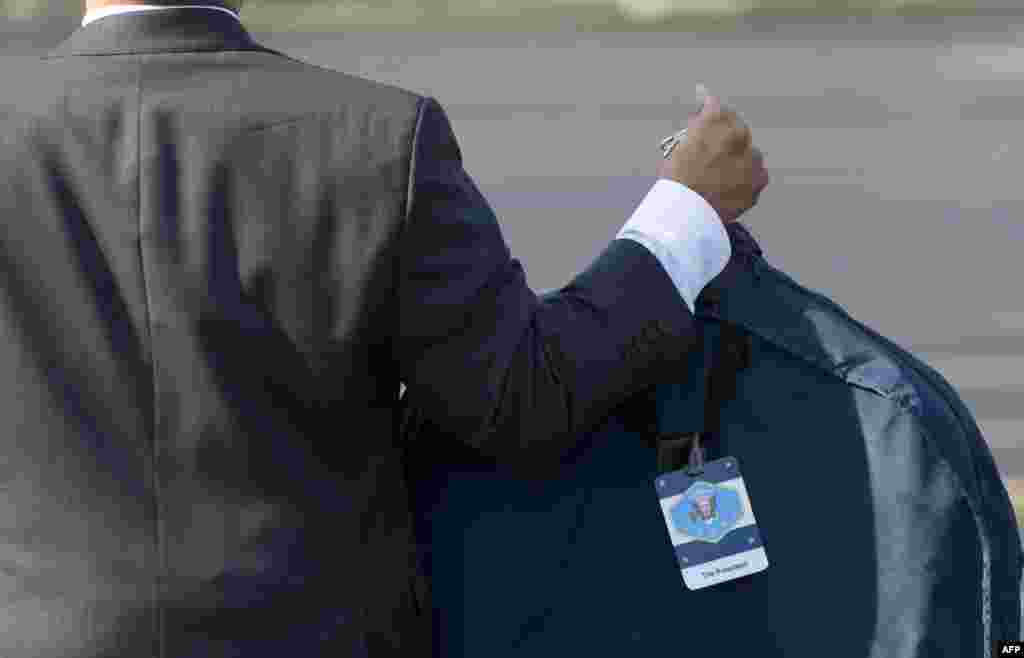 An aide to U.S. President Barack Obama carries the president's suit bag upon arrival in Chicago. (AFP/Saul Loeb)