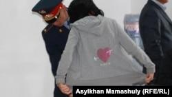 Шетпе соты өтіп жатқан ғимаратқа кіре берісте сотқа қатысушыны тексеріп жатқан полиция қызметкері. Ақтау, 23 сәуір 2012 жыл.