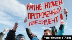 """A demonstrator holds up a sign saying """"We do not need an expired president!"""" at a rally in March 2020 in St. Petersburg."""