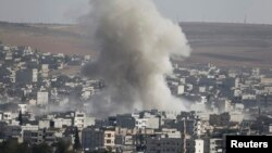 Smoke rises after a U.S.-led air strike on Islamic State positions in the Syrian town of Kobani on October 10.