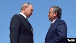 Then-Uzbek Prime Minister Shavkat Mirziyaev (right) speaks with Russian President Vladimir Putin after laying flowers at the grave of late Uzbek President Islam Karimov in Samarkand on September 6.